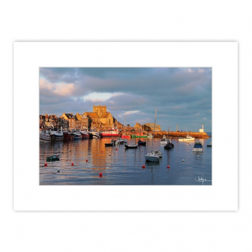 Coucher de soleil de janvier sur le Port de Barfleur, les façades et l'église aux teintes dorées se reflètent dans les eaux du port – Manche – Normandie